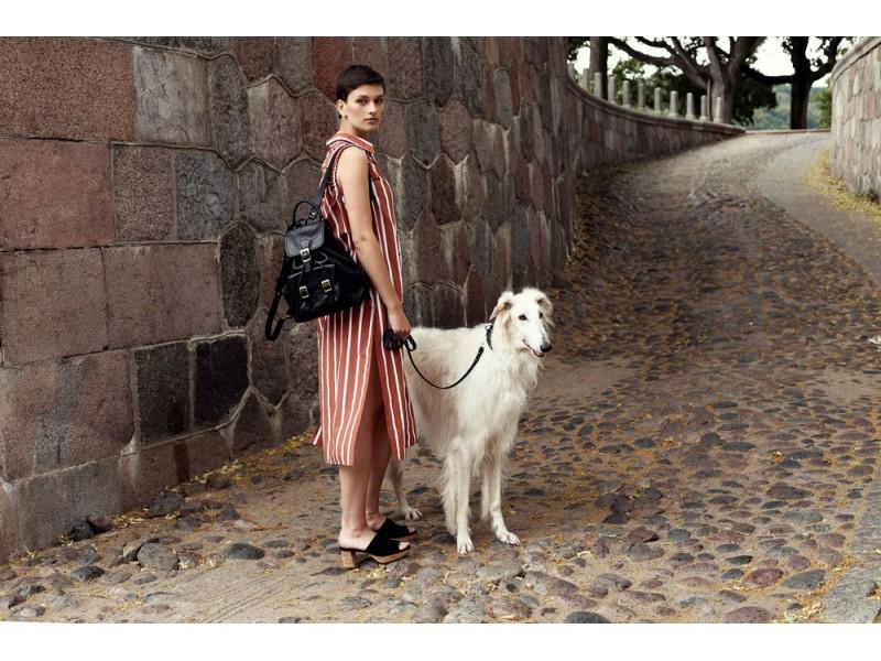 moteris su suniu baltu ir moteriska kuprine senamiestyje